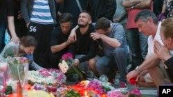 خانواده های قربانیان و ساکنین مونیخ به یاد قربانیان گل و شمع گذاشته اند