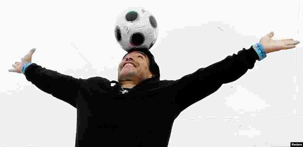 """O ex-astro do futebol Diego Maradona equilibra uma bola de futebol na cabeça durante uma sessão fotográfica para """"Maradona by Kusturica"""", do realizador sérvio Emir Kusturica, no 61º Festival de Cinema de Cannes, 20 de maio de 2008"""
