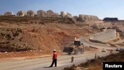ກໍາມະກອນຜູ້ນຶ່ງຢືນຢູ່ໃກ້ລົດດຸດ ໃນຄຸ້ມທີ່ຊາວຢີວຕັ້ງບ້ານເຮືອນ ຢູ່ໃນເຂດ West Bank ຫລືເຂດຝັ່ງຕາເວັນຕົກຂອງ ແມ່ນໍ້າ Jordan ໃນວັນທີ 18 ກໍລະກົດ 2013