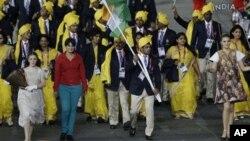 Seorang perempuan tak dikenal (baju merah) ikut bergabung bersama kontingen India di samping pembawa bendera Sushil Kumar, dalam pembukaan olimpiade di London (27/7).