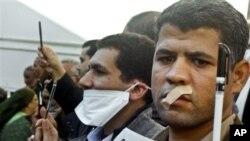 Wartawan Mesir memplester mulut dan mengacungkan pulpen dalam demonstrasi menentang rancangan konstitusi di Kairo (23/12). (AP/Amr Nabil)