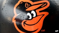 FILE - Rain drops stick to a Baltimore Orioles logo before the team's home opener against the Toronto Blue Jays, April 10, 2015.
