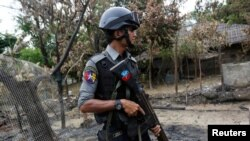 A police officer guards near a house which was burnt down during the last days of violence in Maungdaw, northern Rakhine State, Myanmar August 30, 2017.
