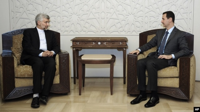 In this photo released by the Syrian official news agency SANA, Iran's Supreme National Security Council, Saeed Jalili, meets with Syrian President Bashar Assad in Damascus,  August 7, 2012.