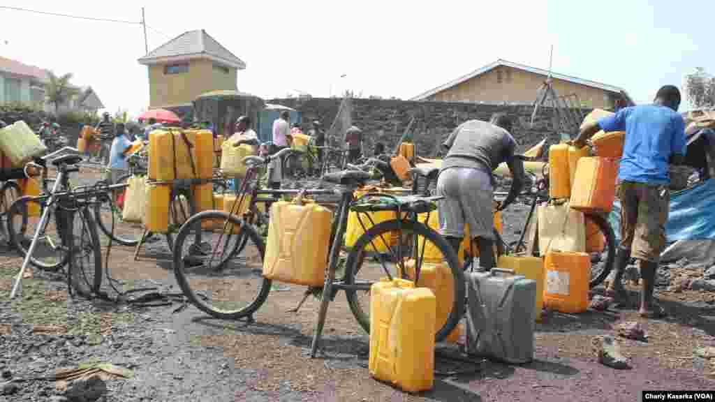Des vendeurs de l'eau puisée du lac Kivu chargent leurs vélos avant d'aller desservir les quartiers non ou mal desservis par la Régie de distribution et traitement d'eau à Goma, Nord-kivu.
