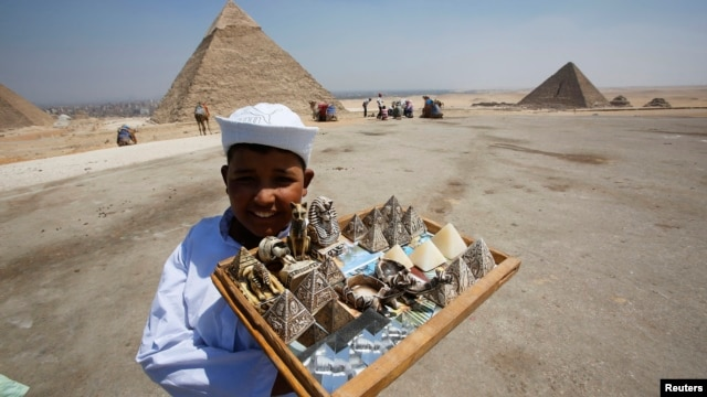 A child vendor waits for tourists to sell them souvenirs at the Giza Pyramids, on the outskirts of Cairo, August 26, 2013.