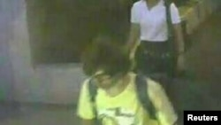 A man wearing a yellow T-shirt and carrying a backpack is seen walking near the Erawan shrine, where a bomb blast killed 22 people on Monday, in Bangkok, Thailand in this handout still image taken from closed-circuit television (CCTV) footage.