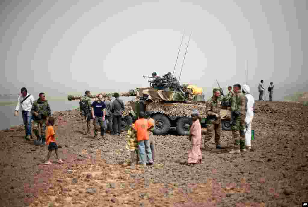 Des habitants de Gao et des journalistes rassemblés près d'un char Sagay positionné près du pont sur le Niger, à l'entrée de Gao.