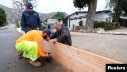 Ingenieros del servicio de campo en California instalan paneles de madera para proteger las casas de posibles inundaciones y deslizamientos de tierra debido a las malas condiciones metereológicas que amenazan varias regiones en California.