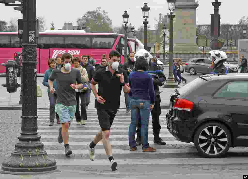 Two joggers wearing protective masks run past a police officer at Concorde Square in Paris, March 17, 2014.