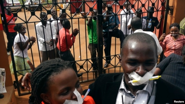 Employees of the Daily Monitor newspaper with their mouths taped shut, sing slogans during a protest against the closure of their premises by the Uganda government, outside their offices in the capital Kampala, Uganda, May 20, 2013.
