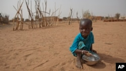 FILE - А boy is seen eating dry couscous in the village of Goudoude Diobe, in the Matam region of northeastern Senegal.