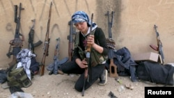 FILE - A female Kurdish fighter from Kurdish People's Protection Units (YPG) checks her weapon near Ras al-Ain, in the Syrian province of Hasakah, after capturing it from Islamist rebels November 6, 2013.