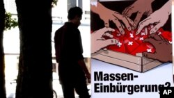 """Seorang pria melewati poster dari partai Swiss People's Party (SVP), salah satu partai yang menentang kewarganegaraan bagi """"warga asing"""" (foto: ilustrasi)."""