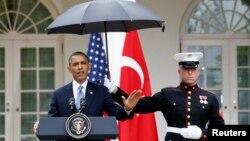 Infantes de marina protegen de la lluvia al presidente Barack Obama, en la Rosaleda de la Casa Blanca.