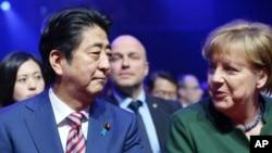 Le Premier ministre du Japon Shinzo Abe est assis aux côtés de la Chancelière allemande Angela Merkel, à l'ouverture du salon CeBIT à Hanovre, en Allemagne, le 19 mars 2017.