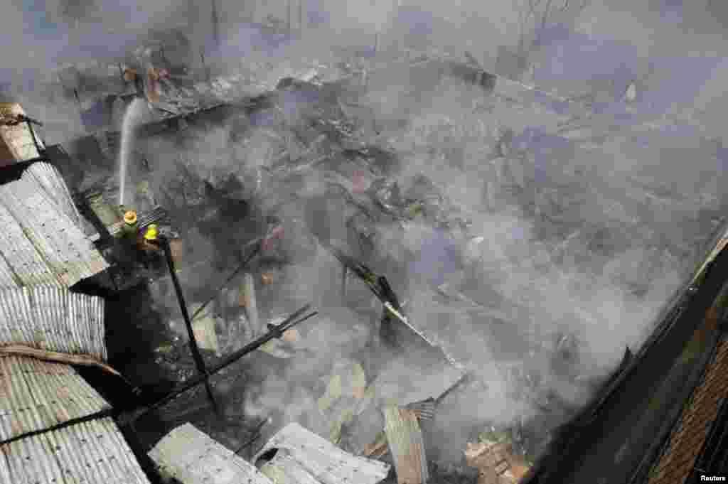 آتشنشانان در حال خاموش کردن آتش سوزی در منطقه حلبی آباد شهر پاسای در حومه مانيل، پايتخت فيليپين. رویترز