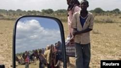 Penduduk Balad, utara ibukota Mogadishu, Somalia, (terlihat dari kaca spion) antri untuk mendapatkan pasokan makanan yang dibagikan oleh gerakan Al Shabaab (Foto: dok).