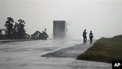 A couple walks along a highway as Hurricane Paula approaches the island in San Cristobal, Cuba, 13 Oct 2010