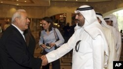 Ông Burhan Ghalioun (trái), lãnh đạo nhóm đối lập SNC, chào những người đến dự cuộc họp ở Doha