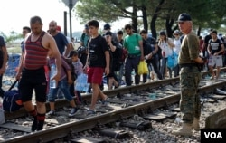 Migrants walk near a camp in the southern Macedonian town of Gevgelija, Sept. 11, 2015.