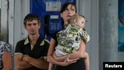 Local residents wait for a bus as they try flee fighting in the eastern Ukrainian city of Slovyansk June 10, 2014.