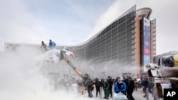 FILE - European dairy farmers spray the EU Council building with milk powder to protest the crisis in their sector, in Brussels, Jan. 23, 2017.