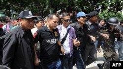 Các thủ lãnh của người biểu tình Áo Đỏ Nattawut Saikuar (thứ nhì bên trái) và Wiphuthalang (nón xanh) bị cảnh sát câu lưu sau khi họ công bố với các ủng hộ viên rằng họ quyết định chấm dứt cuộc biểu tình ở trung tâm Bangkok, ngày 19 tháng 5, 2010