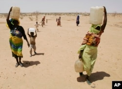FILE - Women carry water across the Iridimi refugee camp near Iriba in eastern Chad, Sept. 25, 2004.