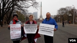Слева направо: Татьяна Лазда, Яна Стрелеца, Ингус Захарченокс. Участники пикета на площади Свободы в Риге. В руках плакаты с требованием освободить из российских тюрем украинских политзаключённых
