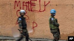 U.N. peacekeepers walk next to a wall with a graffiti in support of presidential candidate Michel Martelly at the Petionville neighborhood in Port-au-Prince, 12 Dec 2010