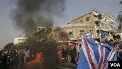 Para demonstran di Teheran membakar bendera Inggris dalam protes di depan Kedutaan Inggris di Teheran, Kamis 4 November 2010.
