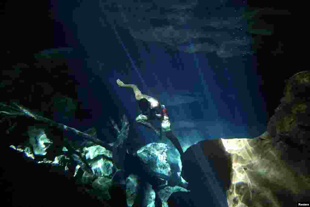 A worker of the cavern of Poco Azul (Blue well) dives to search for belongings dropped by tourists, ahead of World Water Day, in Bahia, Brazil, March 21, 2017.
