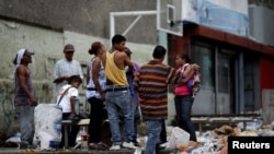 FILE - People search through the garbage on a street in Caracas, Venezuela, Nov. 30, 2016. As the economy suffers, some Venezuelans are forced to forage for food.