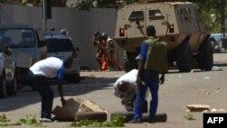 Transeúnes observan mientras personal de seguridad desciende de un vehículo blindado en Uagadugú, la capital de Burkina Faso, el viernes, 2 de marzo de 2018.