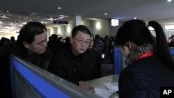 Du khách nói chuyện với nhân viên bán hàng tại một gian hàng cho thuê điện thoại di động Koryolink tại sân bay ở Bình Nhưỡng, Bắc Triều Tiên.