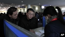 Foreigners speak with sales person about mobile phone service at Pyongyang Airport in Pyongyang, North Korea. (File photo).