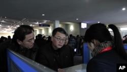 外国人在平壤机场与销售员谈购买手机事宜。(资料照片)