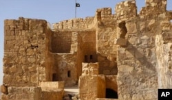 In this picture released May 22, 2015, by the website of Islamic State militants, shows the Islamic State group's flag, top center, raised on the to top of Palmyra castle, in the Syrian town of Palmyra.