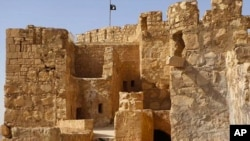 FILE - In this picture released May 22, 2015, by the website of Islamic State militants, shows the Islamic State group's flag, top center, raised on the to top of Palmyra castle, in the Syrian town of Palmyra.
