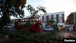 Sebuah bus melewati sebuah pohon yang rubuh di wilayah Islington, London utara, setelah badai St. Jude menghantam wilayah Selatan Inggris (28/10).