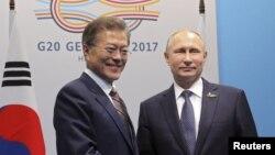 Le président russe Vladimir Poutine et son homologue sud-coréen Moon Jae-In échangent une poignée de main lors d'une rencontre en marge du sommet du G20 à Hambourg, Allemagne, 7 juillet 2017.