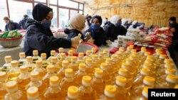 Para relawan dari sebuah badan aman menyiapkan paket-paket bantuan untuk warga yang terdampak pembatasan untuk mencegah penyebaran virus corona (Covid-19), di Damaskus, Suriah, 14 April 2020. (Foto: Reuters)