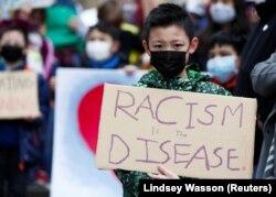 """Ethan Yang, 11, memegang tanda bertuliskan """"rasisme adalah penyakit"""" selama unjuk rasa """"Anak vs. Rasisme"""" melawan kejahatan rasial anti-Asia di Hing Hay Park di Chinatown-International District of Seattle, Washington, AS, 20 Maret 2021 (Foto: REUTERS/Lind"""