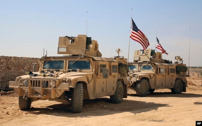 FILE - U.S. forces take up positions on the outskirts of the Syrian town, Manbij, a flashpoint between Turkish troops and allied Syrian fighters and U.S.-backed Kurdish fighters, March 7, 2017.