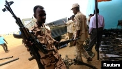 FILE - Rapid Support Forces upload disarmed weapons for display during Sudanese President Omar al-Bashir visit to the war-torn Darfur region at Rapid Support Forces Headquarter in Umm Al-Qura, Darfur, Sudan, Sept. 23, 2017.