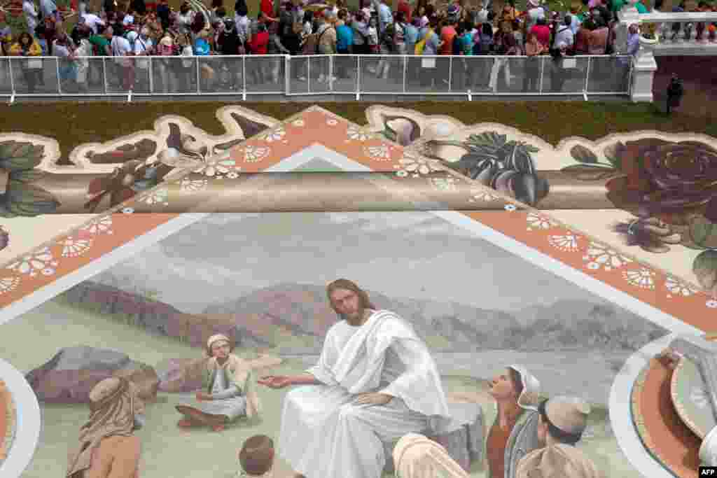Visitors look at a carpet made from sand from the National Park of El Teide depicting Jesus preaching during the Corpus Christi Feast, in the town of La Orotava, on the Spanish Canary Island of Tenerife.