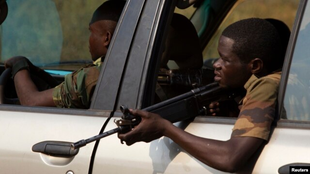 A former Seleka soldier holds his weapon as he keeps guard from a vehicle during an operation of transferring all former Seleka soldiers from their main base Camp de Roux to a smaller base in the north of the capital Bangui on January 27, 2014.