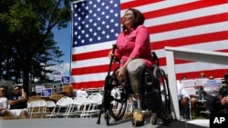 FILE - Democratic Rep. Tammy Duckworth, an Iraq War veteran who lost both of her legs in combat, acknowledges applause from supporters during a rally in Springfield, Illilois, Aug. 20, 2015. Some polls show ahead in her quest to unseat incumbent Republica