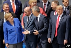 (L-R) German Chancellor Angela Merkel, Belgian Prime Minister Charles Michel, NATO Secretary-General Jens Stoltenberg and U.S. President Donald Trump, watch a fly-by during a summit of heads of state and government at NATO headquarters in Brussels, July 11, 2018.